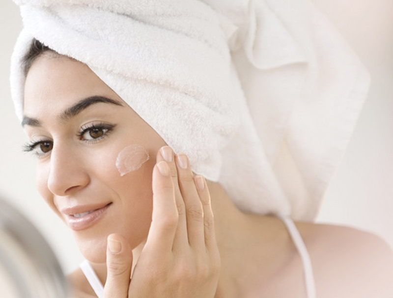 Woman with hair in towel rubbing lotion on face